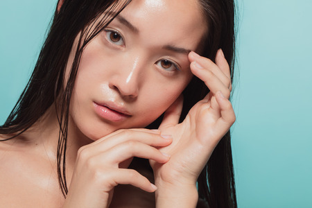 Close up of young asian woman with beautiful skin. Female model with fresh and healthy skin looking at camera.