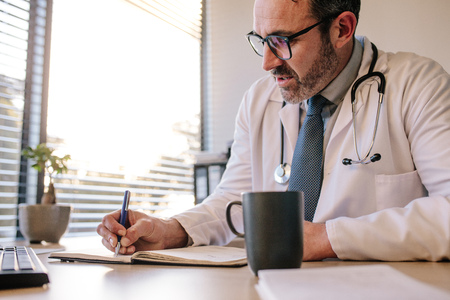 Doctor writing in his diary while sitting at his desk. Male mature doctor writing notes on patient in clinic.