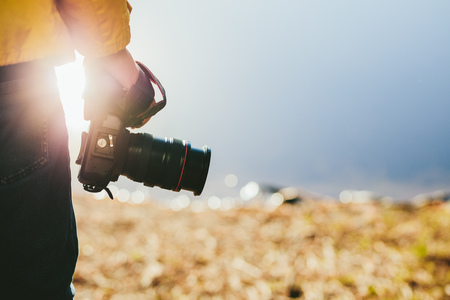 Cropped shot of a man holding a dslr camera in his hand. Rear view close up of hand of a person holding a digital camera with sun flare in the background.