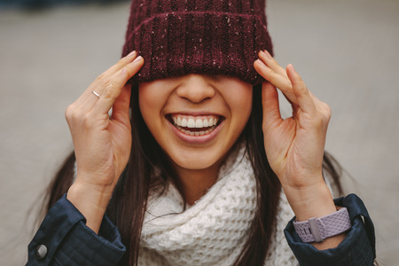 Close up of a smiling woman in winter wear with her face covered with a winter cap. Smiling woman covering her eyes with a len cap. Banco de Imagens