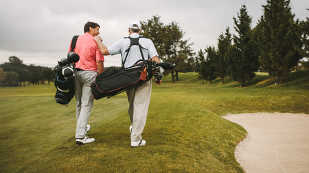 Rear view of two senior golf players walking together in the golf course with their golf bags. Senior golfers walking towards the next hole.