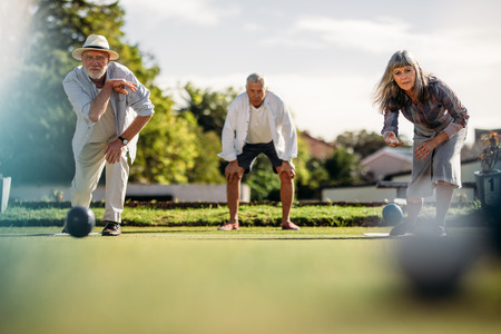 Ground level shot of elderly man and woman playing boules in a lawn with a blurred boules in the foreground. Senior man and woman playing boules competing with each other.