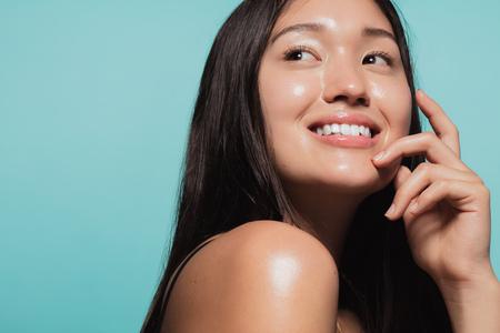 Nahaufnahme eines süßen asiatischen Mädchens mit leuchtender Haut vor blauem Hintergrund. Schönes Gesicht des Mädchens mit frischer gesunder Haut.
