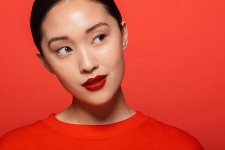Close up of young asian woman with beautiful make up looking away and thinking. Korean female model with red make up against red background.
