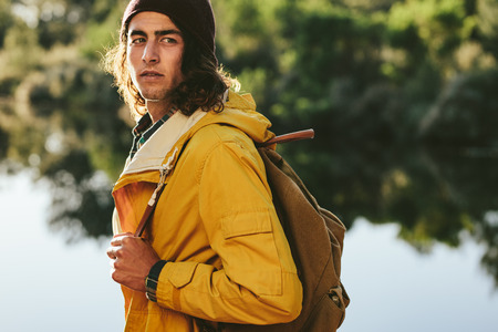 Side view of a traveler wearing backpack standing beside a lake looking away. Close up of a young man standing near a lake on an exploration trip.