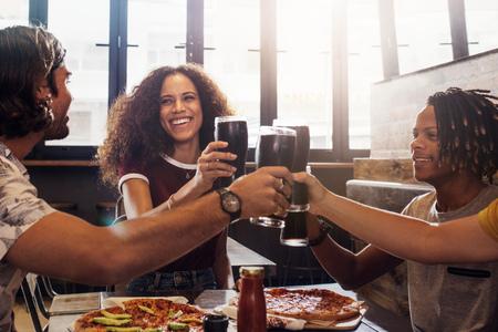 Hombres y mujeres jóvenes sonrientes sentados dentro de un restaurante brindando refrescos. Grupo multiétnico de personas brindando bebidas frías con pizza en la mesa en el restaurante. Foto de archivo