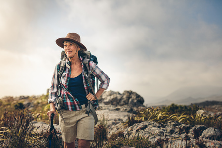 Senior woman trekking down a hill holding trekking pole. Smiling woman walking on a countryside rocky hill wearing backpack. Stock fotó - 118801834