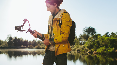 Content creator shooting a video using a mirrorless camera mounted on a hand held gimbal. Side view of a traveler looking at his digital camera to take a photo standing beside a lake. Banco de Imagens