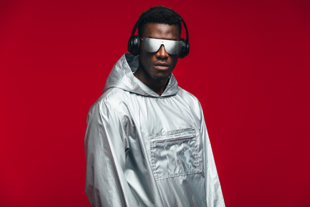 Stylish african man wearing a silver hooded shirt, sunglasses and headphones against red background. Funky young african american guy.