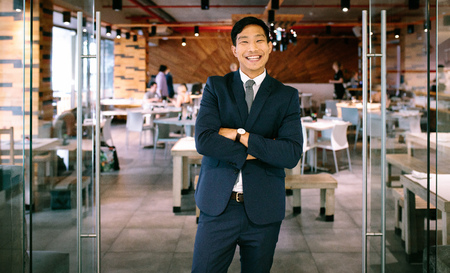 Portrait of cheerful businessman standing at coffee shop with his arms crossed and smiling. Male business professional looking at camera. Stock Photo