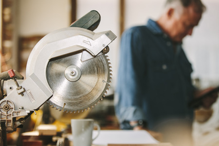 Circular wood saw in carpentry workshop with carpenter in background. Cutting tool in carpentry workshop. 免版税图像 - 118797938