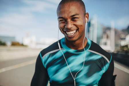 Fit young male runner with a broad smile. Young man in sports shirt and earphones looking at camera.