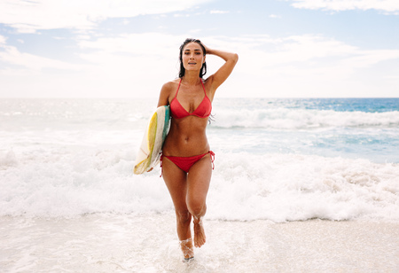 Attractive young woman walking out of the sea carrying a surfboard. Female surfer after surfing in the sea.