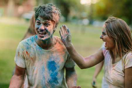 Couple having fun playing holi in a park with friends. Happy woman enjoying holi applying colour to her boyfriend.