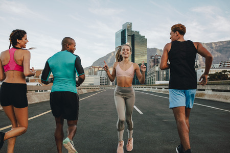Rear view of woman running backwards with her friends on city street. Group of multi-ethnic friends training together outdoors in morning. Stock Photo