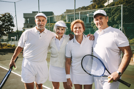 Senior men holding tennis racket and ball standing with their women partners. Seniors standing together holding each other to play mixed doubles tennis match.