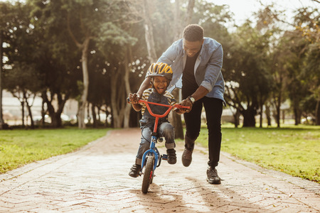 Boy learning to ride a bicycle with his father in park. Father teaching his son cycling at park. Banco de Imagens - 118798557