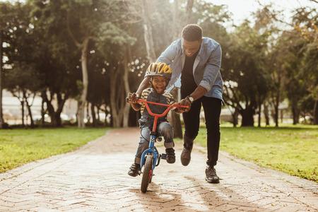 Junge lernt mit seinem Vater im Park Fahrrad zu fahren. Vater lehrt seinen Sohn Radfahren im Park. Standard-Bild
