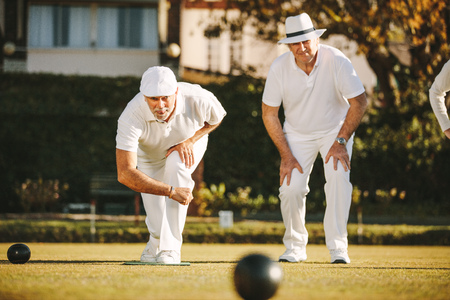 Two senior men playing boules in a park. Elderly men enjoying a game of boules in a lawn on a sunny day.
