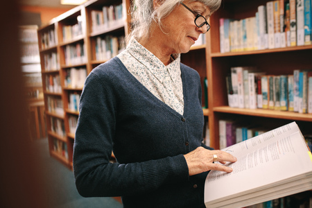 Side view of an elderly woman standing in a library flipping pages of a text book. Senior woman checking reference books standing in a university library.