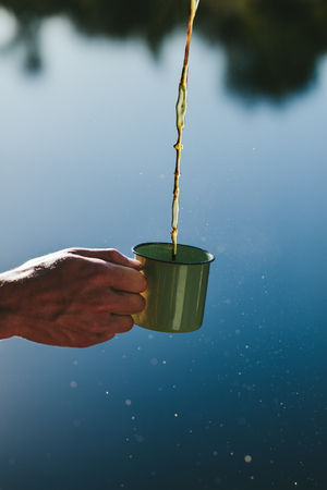 Close up shot of a hand holding a mug with tea pouring in it. Tea being poured in a mug held by a person outdoors.