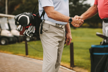 Cropped shot of senior golf players shaking hands when meeting on a golf course. Golfers greeting each other with a handshake before the game.