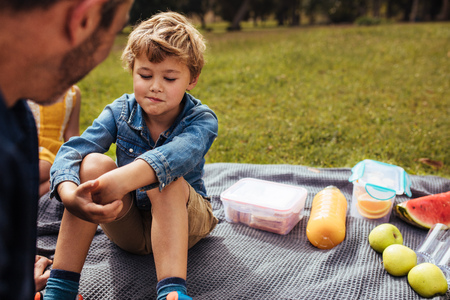 Father consoling his son at picnic in park. Little boy looking upset sitting on picnic blanket with food lying by, listening to his father.