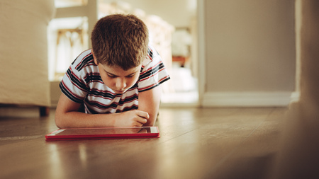 Close up of a boy sitting on floor looking at a tablet pc. Boy using a tablet pc sitting down on floor at home.