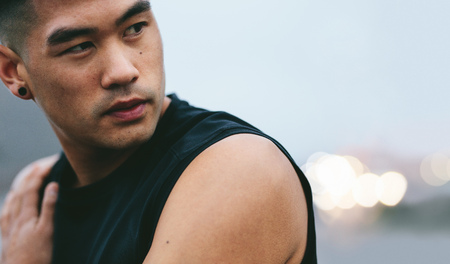 Close up shot of fit young man with muscular build standing outside and looking away. Asian fitness model looking away and thinking.