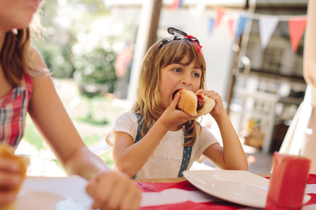 Girl eating a hot dog sitting with her family. Little girl enjoying a hotdog at a restaurant.