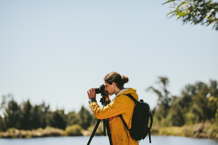 Side view of a photographer looking through his dslr camera mounted on a tripod standing outdoors. Man standing beside a lake taking photos of nature on a sunny day. Imagens