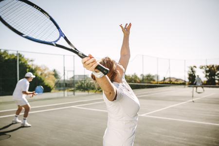 Rear view of a woman serving the ball while playing a mixed doubles tennis match. Men and women playing tennis outdoors on a sunny day. Banco de Imagens