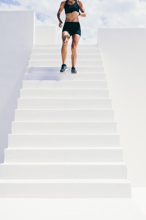 Cropped shot of a woman in fitness wear running downstairs. Fitness woman doing workout running down the stairs of a building. Foto de archivo
