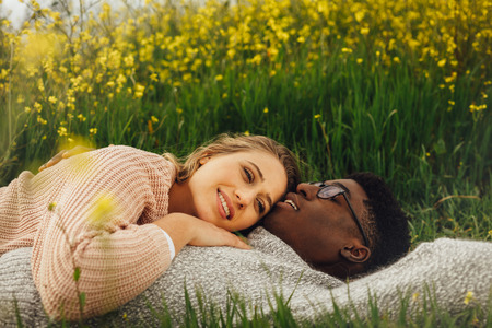 Young interracial couple lying on the grass in meadow. Relaxed young man and woman lying on the grass outdoors.
