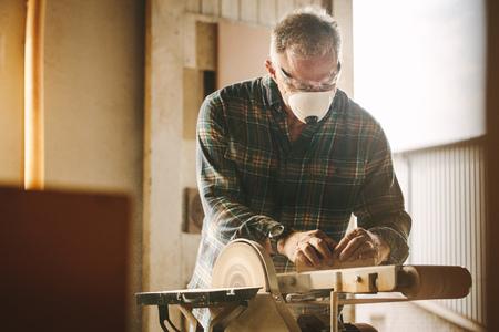 Senior carpenter sanding a wood with belt sander in carpentry workshop. Male carpenter with face mask working on belt sander machine. Banque d'images - 118799370