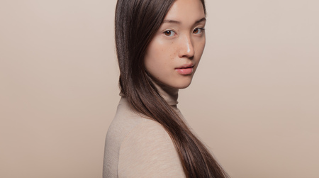 Portrait of beautiful asian woman with brown hair against beige background. Korean female model looking at camera.