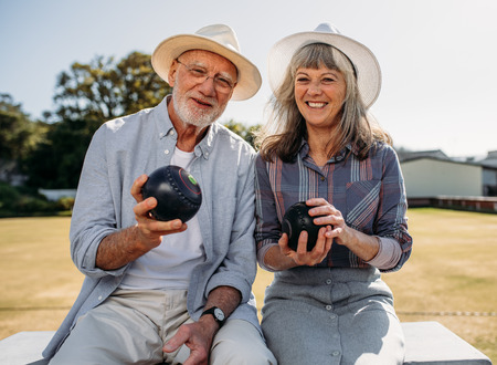 Happy senior man and woman sitting together in a park holding boules. Smiling elderly couple wearing hats enjoying their time sitting in a boules park. Stock Photo