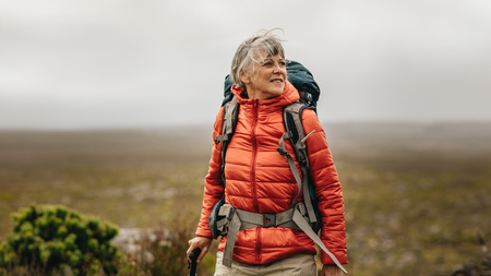 Woman walking on a hill holding a trekking pole. Woman wearing jacket and backpack on a trekking expedition. Stock fotó - 118799510