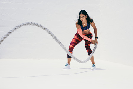 Fitness woman doing strength training using battle rope. Athletic woman doing workout with battle rope.