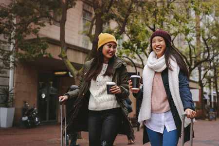 Two asian tourists walking on street with luggage bags enjoying coffee. Cheerful tourist women in winter clothes going around the city having fun. Stockfoto