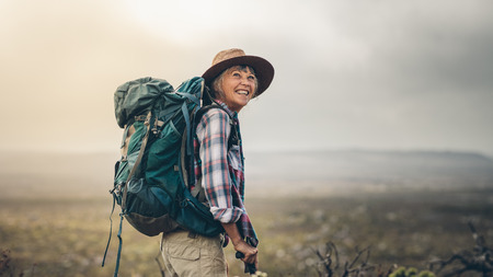 Side view of a senior woman carrying backpack standing on a hill during trekking. Smiling senior woman looking excited during a hiking campaign.