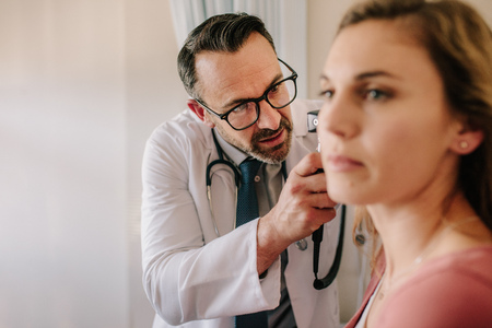 ENT physician looking into female patients ear with an instrument. Male doctor examining patients ear with otoscope in his clinic. Stock Photo
