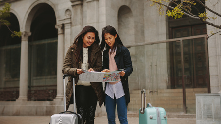 Two asian women tourists looking at a map for navigation. Female tourists standing in street with luggage bags looking for directions in a city map.