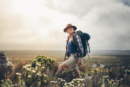 Senior woman standing on a hill wearing a backpack and looking away. Adventure seeking woman trekking through the bushes on a hill.