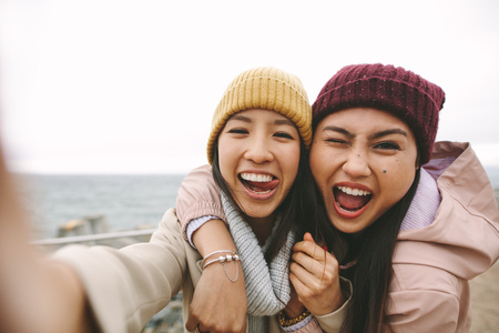 Cheerful asian women in winter wear having fun making faces standing near the sea. Smiling girl friends standing outdoors holding each other on a winter morning.