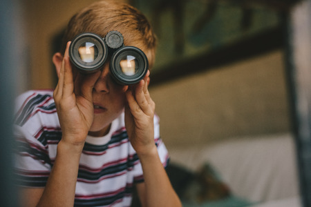 Small boy looking outside window using binoculars. Boy looking through binoculars from the living room.