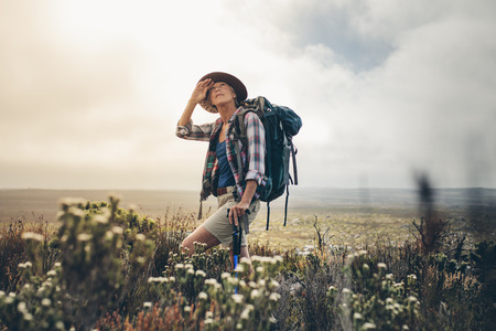 Woman hiker standing in the bushes during her trek looking at the sky. Senior woman on a hiking trip wearing a backpack and hat. Stock fotó