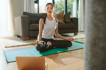 Fit woman doing yoga exercise while watching tutorial on laptop at home. Attractive chinese woman exercising on a mat and watching instructional videos on laptop. Archivio Fotografico