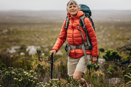 Adventurous senior woman on a hiking trip. Senior woman wearing jacket and backpack trekking in the countryside holding a hiking pole.