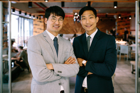 Portrait of two successful business partners standing together at restaurant door. Korean business men standing with their arms crossed and looking at camera.